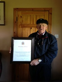 Patsy Dan Rodgers holding the Honorary Masters degree certificate awarded to him from the University of Ulster