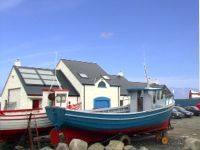 The outside of Bia Cois Farraige at Magheroarty pier showing boats near by